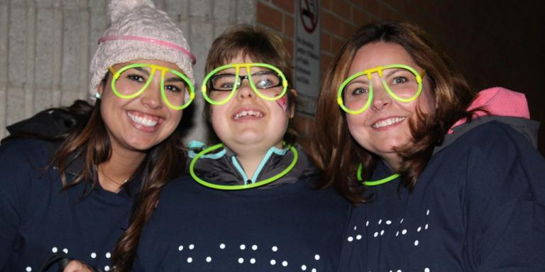 Three participants at Night Steps wearing glow in the dark glasses and smiling.