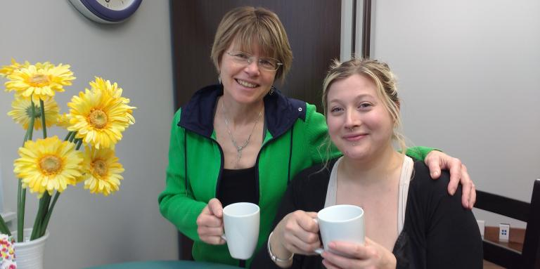 Two women holding coffee cups.