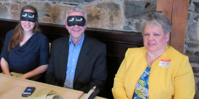 Cindy sits with two Dining in the Dark guests, who are wearing blindfolds.