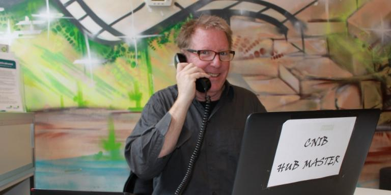 Michael using the phone at his desk at the Hub.