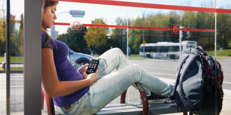 Photo of young woman relaxing, reading an audiobook, waiting at bus stop.