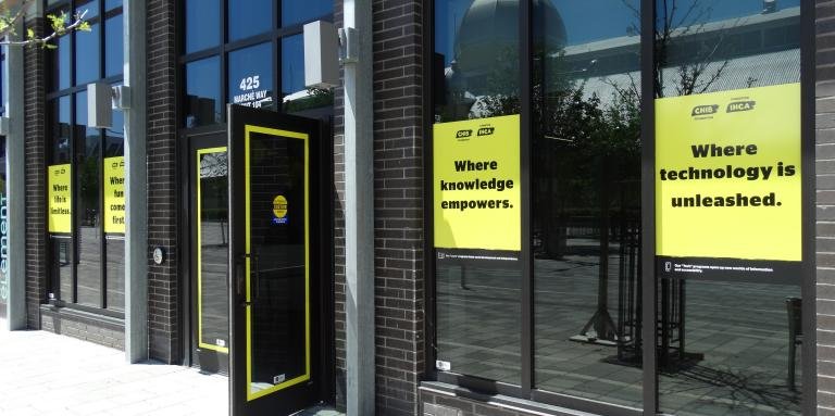 An exterior view of the CNIB Ottawa Hub. A panel of windows. On the windows, CNIB Foundation signage is displayed.