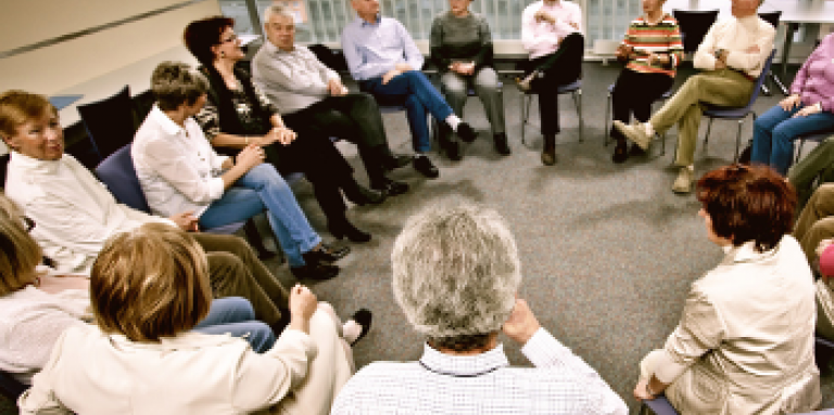 A large group of 17 people gather in a support group. They are seated in a circle.