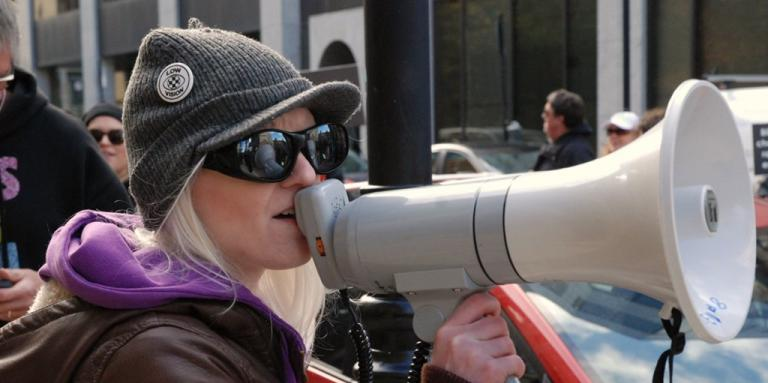 A woman holds a megaphone to her mouth.