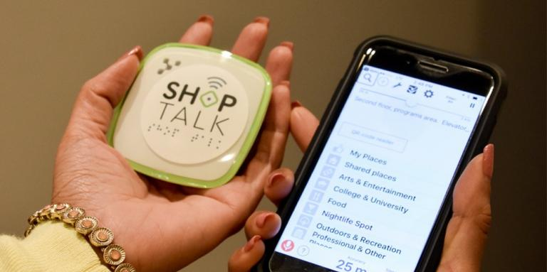 A woman holds a shop talk beacon in one hand and a smartphone in another.