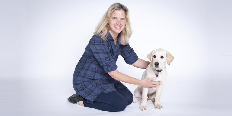 A woman kneeling beside a Golden Retriver puppy.