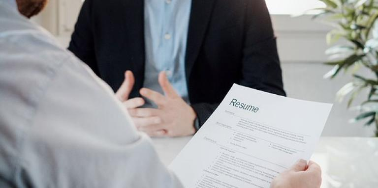 A job interview. An employer holds a resume. In front of him is someone being interviewed.