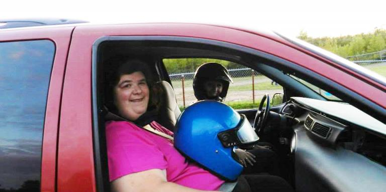 Julie Morneault sitting in a red truck with a blue motorcycle helmet on her lap.