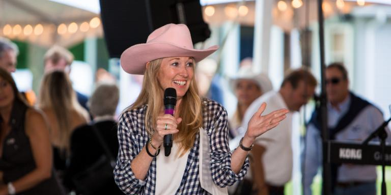 Nancy Simonot wearing a pink cowboy hat and speaking into a microphone at a Lake Joe fundraising event.