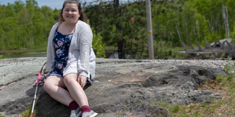 Alicia smiles and sits outdoors on a large rock. Behind her are trees. She is wearing a summer floral dress. Her white cane rests on the rock to the right of her.