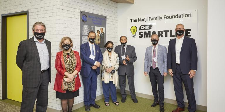 From left to right, John Rafferty, President and CEO of CNIB, Eyre Purkin Bien, Senior advisor, Philanthropy, three members of the Nanji Family, Garry Nenson Vice President of Philanthropy for CNIB, and Shane Silver, Vice President of Social Enterprises for CNIB. The group stands together in front of the new Nanji Family Foundation CNIB SmartLife Centre.