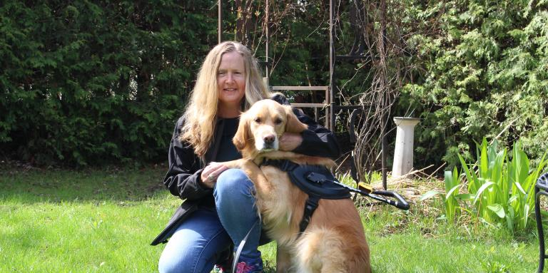 Diane Bergeron kneeling on grass next to her guide dog Carla, a golden retriever.