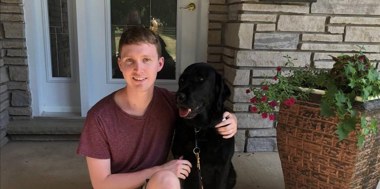 Jack McCormick sitting on the front step of house with his arm around his guide dog sitting at his side.