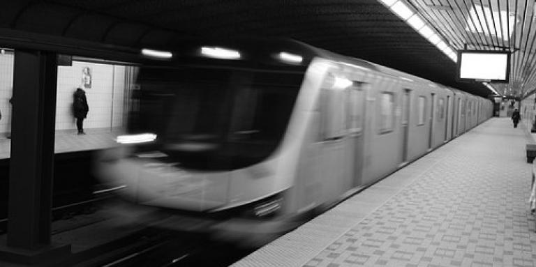 A blurry subway car breezes into a station.