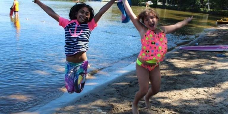 Two girls holding hands, smiling, and jumping at the water's edge.