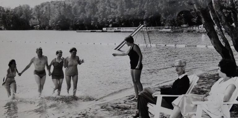 An old black and white photograph of people at CNIB Lake Joe running into the lake.