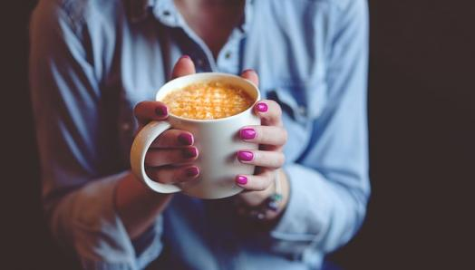 A woman's hands firmly grip a piping hot cup of coffee.