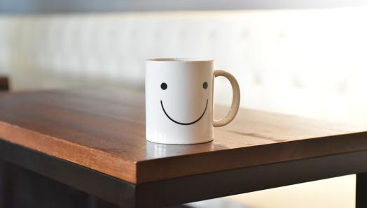 White coffee mug with a smiley face on it, sitting on a wood table