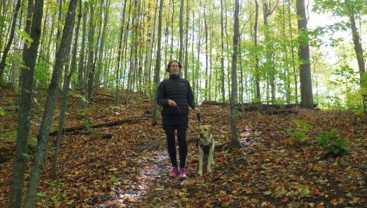 Marie-Claire and Rhonda, walking through a lush, green forest – the ground covered with colourful autumn leaves.
