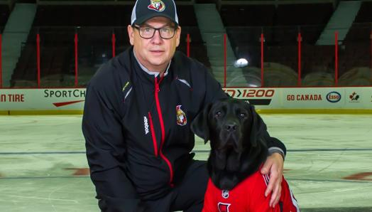 Mark Kelly kneeling next to Rookie, a Future CNIB Guide Dog wearing an Ottawa Senators jersey, with his arm around Rookie while they both smile for the camera. They are on a red carpet laid over the ice of the Canadian Tire Centre, home to the Ottawa Senators.