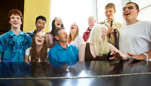 Walter Gretzky sits at a grand piano surrounded by 9 youth with sight loss. They are smiling and excitedly singing a tune while Walter plays the piano.