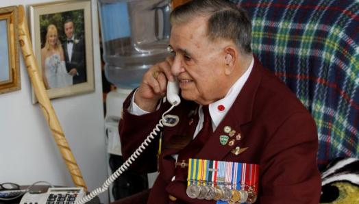 Older man smiles while talking on the phone